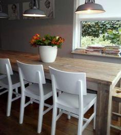 Landelijke eettafel met bankje in de keuken . mooi met witte stoelen en houten tafel
