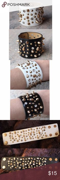 "Black OR White Gold Studded Skull Wristband These bracelets are so edgy and fun! (This listing is for 1 bracelet - the one with the white band or the one with the black band). Embellishing them are a mix of gold studs, circles, crystals, and skulls. They are made of leatherette, metals, and crystals and have 2 double snap closures. They fit a 7"" or 8"" wrist. The width of the bracelets measures 2"". They are brand new in the original packaging from B&B Couture. B&B Couture Jewelry Bracelets"