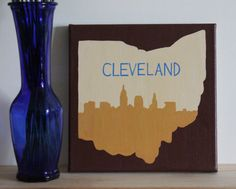 Handmade wine and gold Cleveland, CLE, Ohio Cavs/Cavaliers basketball championship winners art home decor with the outline shape of the state of Ohio in black on an 8 in x 8 in canvas with a maroon painted background and matching edges.  This canvas is a perfect piece for any proud Ohioan or Ohio lover - especially the proud Cavs fan in your life!  Canvas is ready to be hung or framed. I usually hang my canvases using command strip products as they are much less damaging to the wall…
