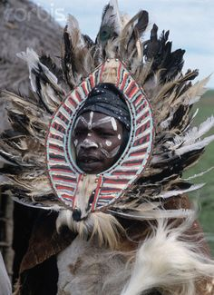 Africa | Kikuyu man wearing a feather mane with a painted face and wrapped in animal hides. Near Aberdare Mountains, Kenya. | ©Buddy Mays