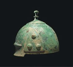 A CELTIC BRONZE HELMET  3RD-2ND CENTURY B.C.  Of domed form with attached tall knopped finial, moulded inverted-V ribs above the brow extending into encircling band around the crown, each side with three raised decorative bosses, with dents