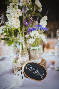 Pretty wild flowers table centre pieces in recycled jam jars.  From 'A Wildflower and Woodland Inspired Rustic, Rural Barn Wedding' on www.lovemydress.net, photography by http://www.claudiarosecarter.co.uk/