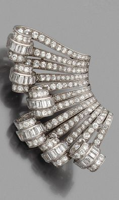A pair of Art Deco platinum, white gold and diamond clip brooches, French, about 1930. Length 7cm.