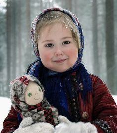 A smiling girl has a doll in her hands. The girl is dressed in Russian shawl and a warm coat.