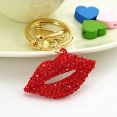 Crystal Bling Kiss Lips Purse Charm & Keychain Crystal Bling Kiss Lips Purse Charm & Keychain  Sparkling red crystal kiss lips purse charm/keychain beautifully designed with gold and red metal, and embellished with red rhinestone crystals. Includes a key ring & secure lobster clasp for versatile use as a keychain, purse charm, backpack and more. Materials: Zinc Alloy Metal & Rhinestone Crystals, Measurements: 3.5 x 2 in., Light Weight: 1 oz. Bling Car Decor Accessories Key & Card Holders