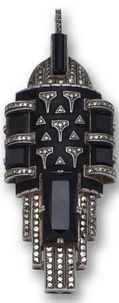 An Art Deco onyx, marcasite and enamel pendant, Theodor Fahrner, circa 1929. The geometric pendant centring a plaque of matte black enamel with marcasite detail flanked by two square onyx and bordered by rectangular onyx and marcasite lines; with maker's mark TF for Theodor Fahrner; mounted in silver. #Fahrner #ArtDeco #pendant
