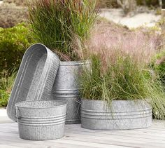 """Eclectic Galvanized Metal Planters  $69 Planter Box: 30"""" wide x 10.25"""" deep x 9"""" high; 6lbs tilted up  against XL barrel. $79 Medium Round: 18""""dia. 11.5""""ht; 4.5lbs Left most in front. $89 Large Oval: 30.5"""" wide x 17"""" deep x 11""""ht; albs handles w/ pink muhly grass (shorter grass) on rt. $149 Extra-Large Barrel: 20"""" dia, 24"""" high; 10lbs Back middle w/ purple tinged grass (tallest grass) in it. OK"""