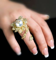 What do you think of this ring? Diamonds in gold, designed as a flower with a pearl center. (Via 1stdibs.)