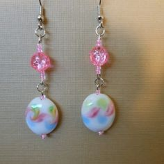 Use the coupon code WEAREOPEN to save 10% on orders overs over $15 as a GRAND OPENING SPECIAL... Stainless steel hook earrings with clear pink plastic textured beads, small clear pink glass seed beads and a large white glass bead with pink, green & blue swirls.