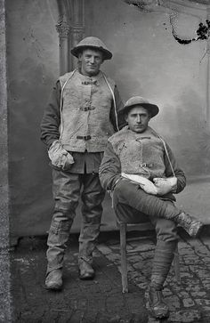 WWI; Portrait of two unidentified Australian soldiers of the 1st Division wearing sheepskin vests and mittens to ward off the cold. The standing soldier wears rubber over-pants.