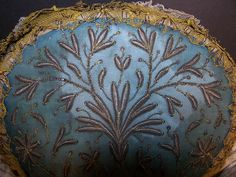 Folk haube dating from the mid 1800s. It is made of a rigid rag linen base covered with a blue silk fabric and silver metallic accents. The metallic threads are hand stitched in a raised padded satin stitch embroidery couching work floral leaf design. Bavaria