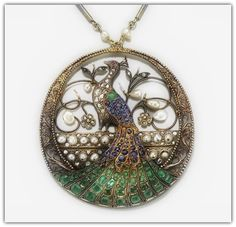 This unique and lovely Art Nouveau-era pendant features a stunning, sweeping Peacock decorated with emeralds, sapphires and natural pearls mounted in gold. The scrollwork around the frame is just perfect (and of course, a hallmark of the Nouveau style!).