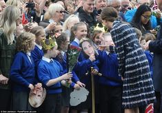 Kate looked utterly charmed as she pointed to a little girl who had a mask of her own face, as if to say: 'Is that really me?'