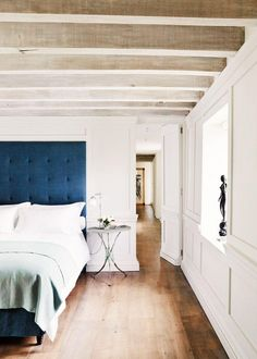 Dark blue headboard on white bedding and almond green duvet, with delicate iron tripod nightstand, traditional white millwork on the walls, and whitewashed exposed beams on the bedroom ceiling.