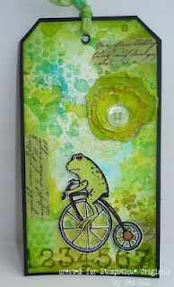 Tag: green tones, frog on tricycle, numerals, paper floral. Gez Butterworth