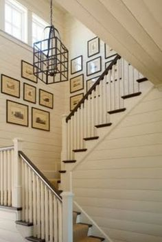 This fantastic stairway wall grouping features beautifully custom framed photos, which mimic the lines of that amazing chandelier - a perfect balance.