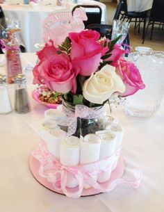 Baby Shower Centerpieces - These very cute and easy centerpieces are made by rolling diapers and placing them around a mason jar that is filled with a flower bouquet, which can be removed and given to guests as prizes. Add ribbon and decorative items to create an adorable centerpiece/gift!