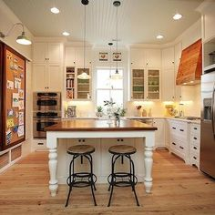 Kitchen Cork Board, white cabinets, stools, wood range hood, beadboard ceilings