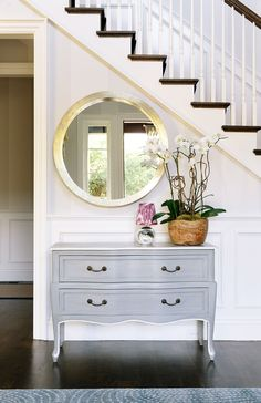 Console table under white staircase with round mirror and orchids