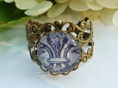 Filigraner Ring aus bronzefarbenem Metall und einer Fassung, die mit einem handgearbeiteten Glas-Cabochon besetzt ist. Das Metall des Rings ist sehr b