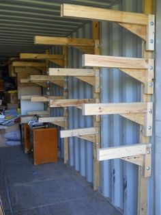 Homemade cantilevered shelving system intended to fit in a shipping container, the shelf units feature legs anchored to the wall via the tie-down points. The brackets are and the plywood was glued in place. Storage Shed Organization, Garage Storage Shelves, Workshop Storage, Built In Storage, Barn Storage, Shed Shelving, Storage Sheds, Tool Storage, Shipping Container Workshop