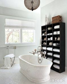 An Urban Archaeology tub, a Waterworks tub filler, and an early-20th-century French steel bookcase in the master bath; the 1940s chandelier is by Lobmeyr, and the walls are painted in Benjamin Moore's Paper White.