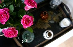 A wooden tray with fresh pink roses, vases and a candle