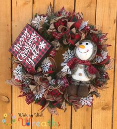 """This cute buffalo plaid snowman wreath is the perfect wreath for farmhouse and country themed decor. This adorable snowman wreath sits on an evergreen base with strips of burlap surrounding the base. This Snowman Wreath contains a cute Buffalo plaid Sign reading """"Merry Christmas Ya'll"""" opposite the sign sits a cute snowman dressed in a maroon jacket and hat ready for the winter weather!"""