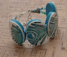 Peacock feather cuff/bracelet. Handmade polymer clay beads on memory wire for strength and hand painted with liquid polymer custom color tinted with mica powders.