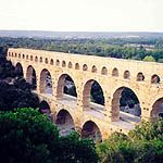 "Pont du Gard Commentary   ""This bridge, over the river Gard, is 275 metres (900 feet) long and 49 metres (160 feet) high. It was part of an aqueduct nearly 50 kilometres (30 miles) long which supplied Nimes with water. On its first level it carries a road and at the top of the third level, a water conduit, which is 1.8 metres (6 feet) high and 1.2 metres (4 feet) wide and has a gradient of 0.4 per cent. The three levels were built in dressed stone without mortar. The projecting blocks…"