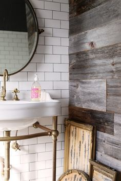 Chic bathroom features round pivot mirror on subway tiled wall accented with dark grout paired ...
