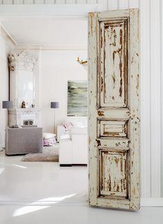 Upeat pariovet yhdistävät keittiön ja olohuoneen. Seinällä on Riikka Soinisen öljyväriteos.