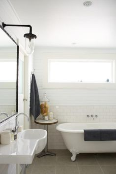 Clawfoot tub, subway tile, industrial light over the mirror @Justine Hugh-Jones's Sydney cottage