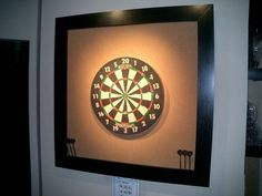 """Dart Board Surround. DIY project out of cork bulletin board & 2"""" rigid foam board in a wood frame. Hung with a french cleat for stability. Cool!"""