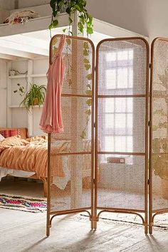 Screened room divider crafted from rattan for a perfectly boho way to break up any space. Great in a living or sleeping space!
