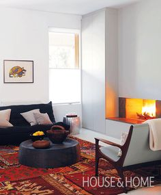 A red and ochre rug is the perfect cozy counterpoint to the sleek fireplace in this living room. Living Room Decor, Living Spaces, Beautiful Home Designs, Room Planning, Modern Spaces, Colorful Interiors, Diy Home Decor, House Design, Interior Design