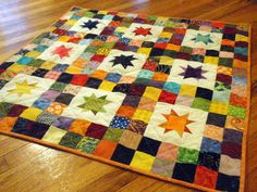 Starry Skies Baby Quilt - With its vibrant colors and simple shapes, this Starry Skies Baby Quilt looks like it came right out of a children's book. By following this star quilt pattern, you'll create star block patterns surrounded by blocks of colorful fabric. Use this pretty piecework project to welcome a new baby into the world. After all, nothing beats a handcrafted gift that was made with love.