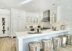 California Beach Cottage. Kitchen: This white coastal kitchen features a kitchen peninsula topped with white marble framing farmhouse sink and satin nickel faucet.