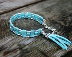 This bracelet features pretty turquoise Czech glass tiles that have been strung onto sections of memory wire and formed into a cuff. Tiny faceted silver beads and a matching turquoise tassel with a pretty silver bead cap have been added to complete the look. The bracelet includes a bright silver safety chain, and will fit wrists up to about 7 1/2 inches around. The glass tile beads measure about 3/16 inches (or 5 mm).