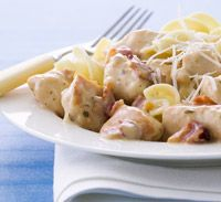 Creamy Ranch Chicken  6    slices bacon      4   skinless, boneless chicken breast halves, cut into bite-size pieces      2    tablespoons all-purpose flour      2 tablespoons ranch dry salad dressing mix      1 1/4    cups whole milk      3    cups dried medium noodles      1 tablespoon finely shredded Parmesan cheese