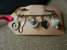ALICE IN WONDERLAND INSPIRED KILT PIN BROOCH WITH CHINA TEA-SET AND CHARMS