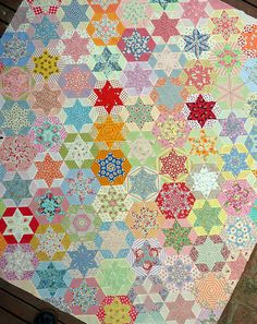 hexagon blocks are made using just one diamond shaped template to cut fabric pieces.  Most  fabrics were carefully fussy-cut to create a repeat pattern in the center star.  The quilt top is entirely hand pieced.