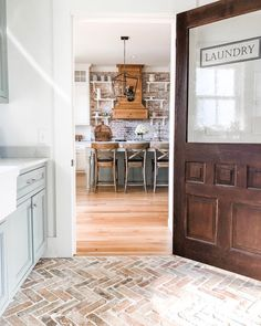 Cute farmhouse kitchen from the perspective of the GORgeous laundry room complete with rustic zigzag red brick flooring. 💞💕💞 Love the open shelving on brick in the kitchen and the dramatic wood hood vent. Mudroom Laundry Room, Large Laundry Rooms, Laundry Decor, Laundry Room Design, Small Laundry, Home Design Diy, Küchen Design, House Design, Sweet Home