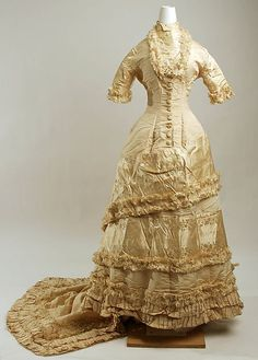 This is an American wedding dress from 1878-79. It is gold, which was a very popular color at the time for wedding dresses, and features a long train, asymmetry across the skirt, and a mandarin collar, which were all popular during the bustle period. This dress can be found at the Met.