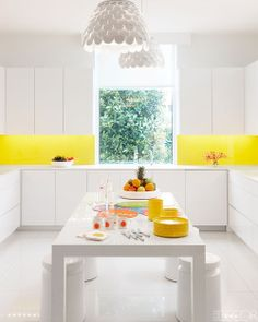 Embracing white space, designer Lisa Perry's kitchen focuses on a backsplash of yellow that creates depth in the room.