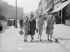 Four young ladies enjoy a stroll in the Spring sunshine along a shopping street in the West End of London. Two are wearing fancy hats, proving that wartime clothing doesn't have to be drab! Cars and other pedestrians go about their daily business behind them.    Label  Four young ladies enjoy a stroll in the Spring sunshine along a shopping street in the West End of London during 1941.