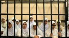 Prison sentences for women in Egypt .This is a mid shot photo. We can notice that these women are sad as we see on their faces . They are all wearing the same white uniform and seem like waiting for being released from prison or they are expecting some visitors.