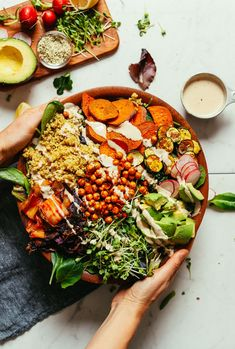 Large salad serving bowl with fresh greens, vegetables, chickpeas, and savory tahini dressing