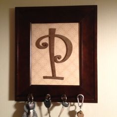 """DIY Keyholder. Scrapbook paper in frame with a painted wooden """"P."""" Wooden pegs to hold keys!"""