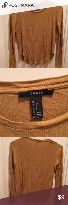 Forever 21 Mustard Yellow Long Sleeved Tee This long-sleeved t-shirt from Forever 21 is in a mustard yellow color, has a curved hem, and is made of a ribbed material. Size S. Buy 2 or more Forever 21 shirts in my current listings together and get a discount. Forever 21 Tops Tees - Long Sleeve